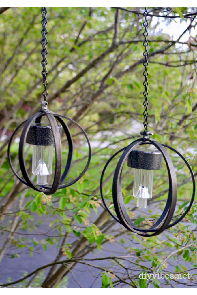 Two hanging solar lights on a tree