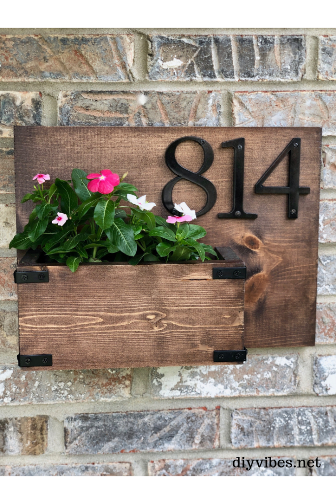 wooden house number sign with pink flowers